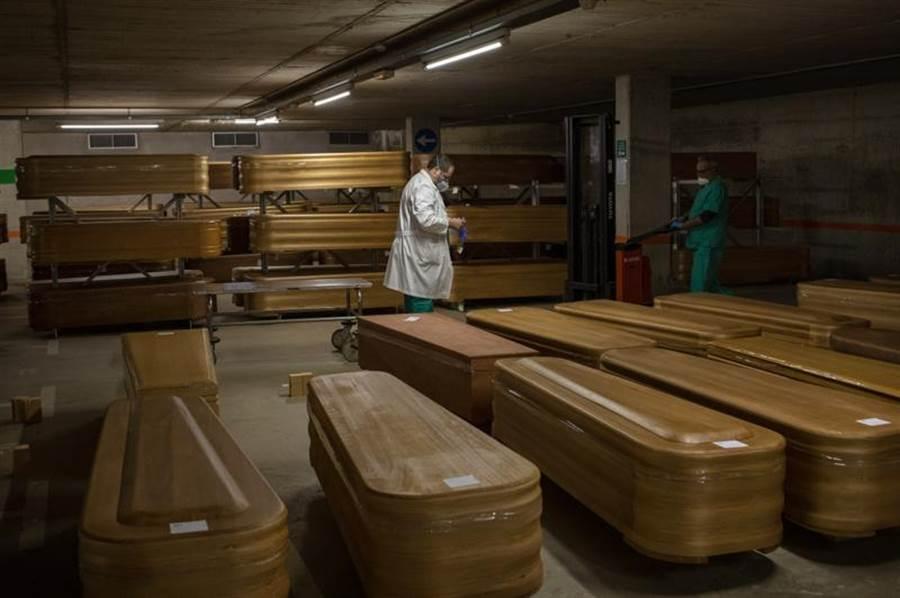 圖為在西班牙醫院準備給因新冠病毒病逝者的棺材。(美聯社)