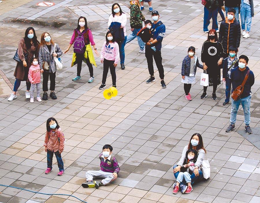 新冠肺炎疫情未歇,2日民眾趁著清明連假首日逛街購物,在廣場上駐足停留觀賞街頭藝人的扯鈴表演,雖然人潮不若以往又在戶外,但幾乎人人都配戴口罩,並保持社交距離,做好防疫措施。(黃世麒攝)
