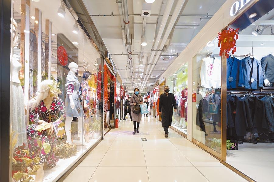 出入公共場所最好戴口罩,圖為3月1日,民眾經過北京秀水街商場。(中新社)