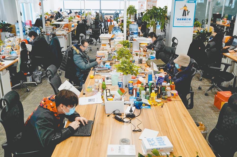 專家籲在辦公室內務必戴口罩,圖為3月5日,北京一互聯網公司員工戴口罩並以「W型入座」方式就座辦公,加大彼此間隔。(中新社)