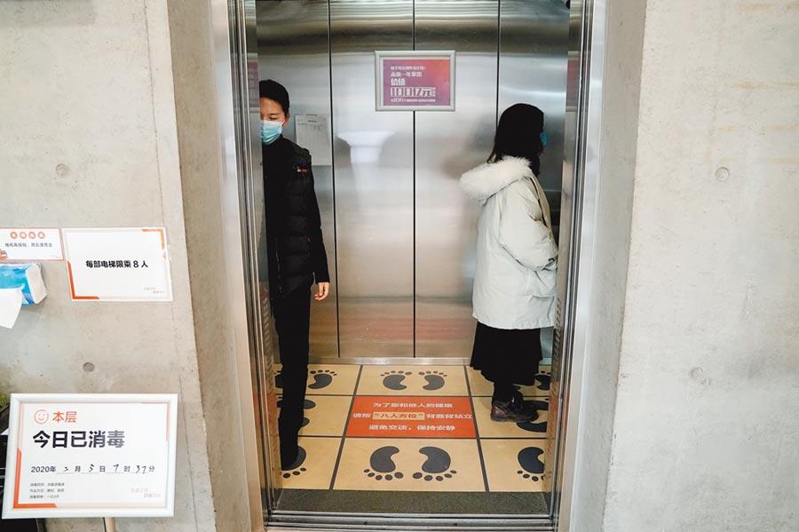 電梯的密閉空間易感染病毒,圖為3月5日,北京一公司員工按照劃定區域乘坐電梯。(中新社)