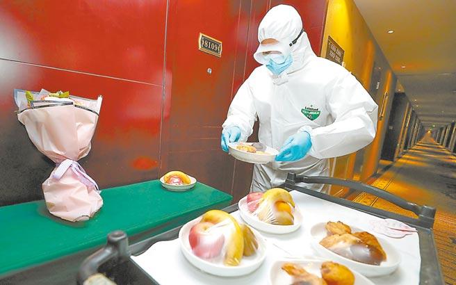 在集中觀察酒店,工作人員將贈送的暖心水果、點心及鮮花送至房間門口。(武亦彬攝)