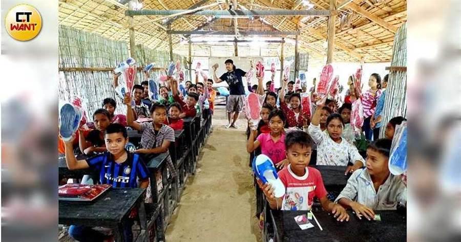 毛弟與姊姊發起「藍白拖計畫」,2013年10月姊弟兩人送愛心到柬埔寨。(圖/讀者提供)