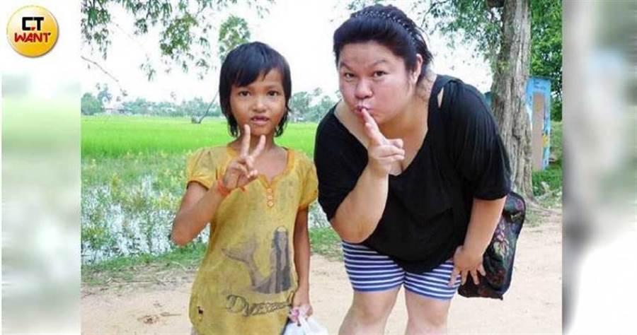柬埔寨的孩子們接過有圖案的鉛筆,卻怕毀了上面的卡通圖案而不敢用,讓毛弟跟姊姊(右)立下心願要幫助更多人。(圖/讀者提供)