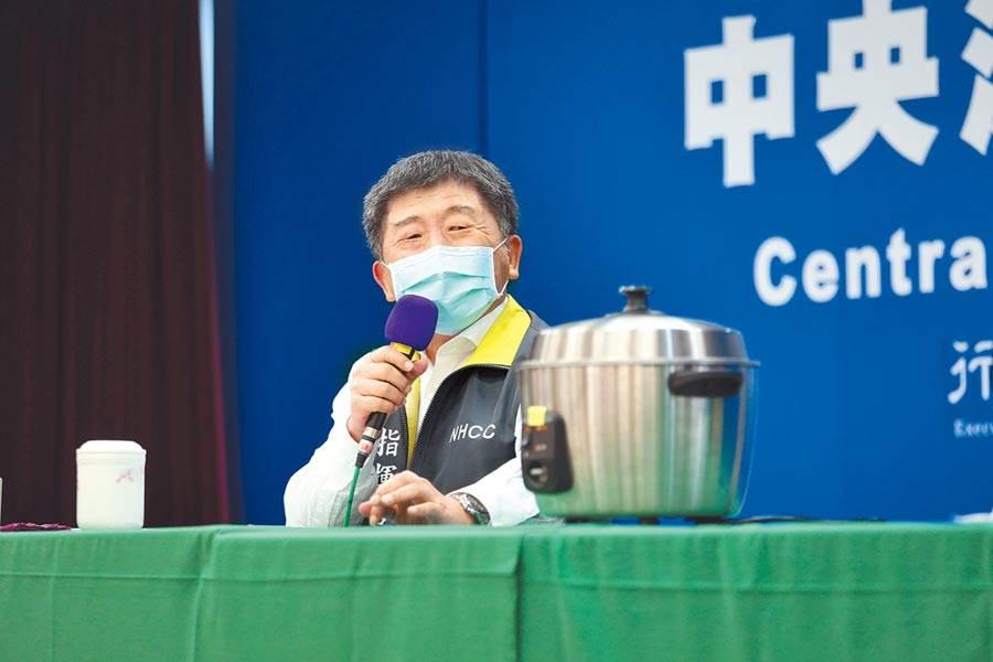 中央流行疫情指揮中心5日在記者會上,示範如何用電鍋乾蒸口罩,指揮官陳時中也現場試戴「剛起鍋」的口罩,他大讚「熱熱的不錯」,並掛保證乾蒸後的口罩完全無異味。(中央流行疫情指揮中心提供)
