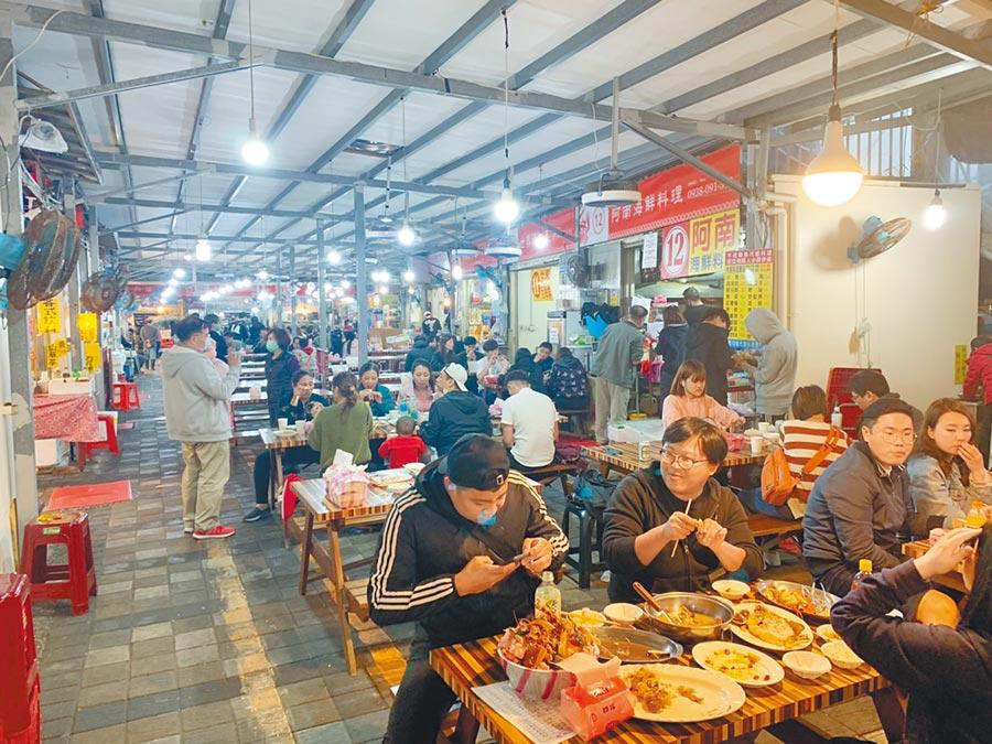龜吼漁夫市集利用降價方式吸引遊客來品嘗道地海鮮,效果甚佳,遊客回流達5成。(張睿廷攝)