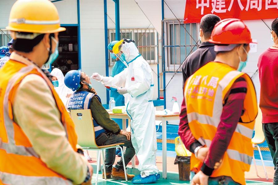武漢封城76天後,今天零時起解除,恢復對外交通。圖為檢測人員為復工人員進行採檢。(中新社)