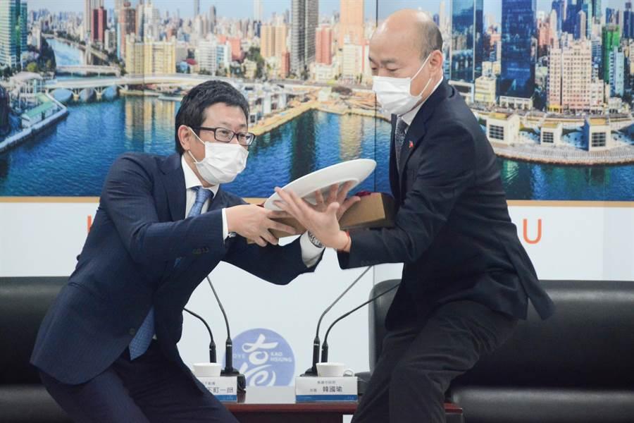 高雄市長韓國瑜(右)送瓷盤給台灣三井不動產董事長下町一朗(左),過程中瓷盤不慎滑落,差點掉到地上。(林宏聰攝)