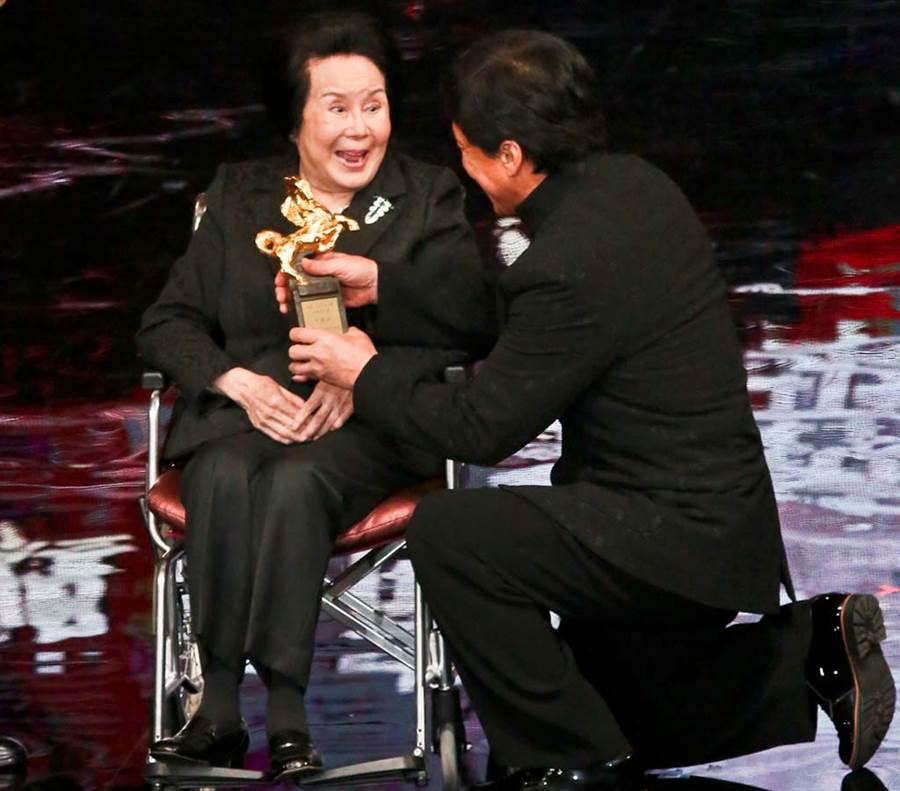 成龍50年來一直喊李麗華為「媽媽」,2015年跪著為她遞上金馬獎終身成就獎。(中時資料照片)