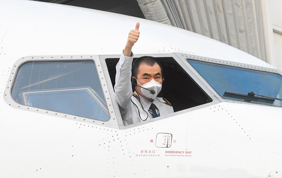 4月8日,在武漢天河國際機場,東方航空飛行員在起飛前致意。(新華社)