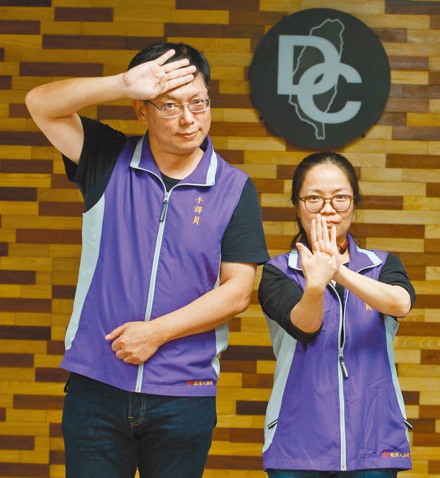 參與疫情記者會的手語翻譯員打出「防疫加油」手語,李振輝(左起)打「疾病」、林亞秀打「對抗」。(陳怡誠攝)