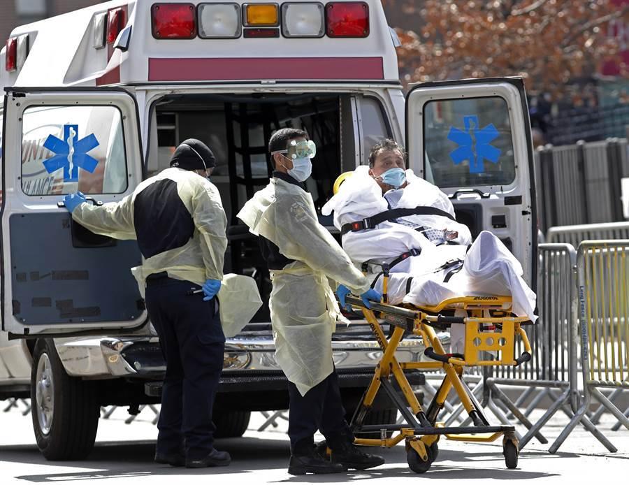 一名新冠肺炎病患7日在紐約皇后區被送上救護車。(美聯社)