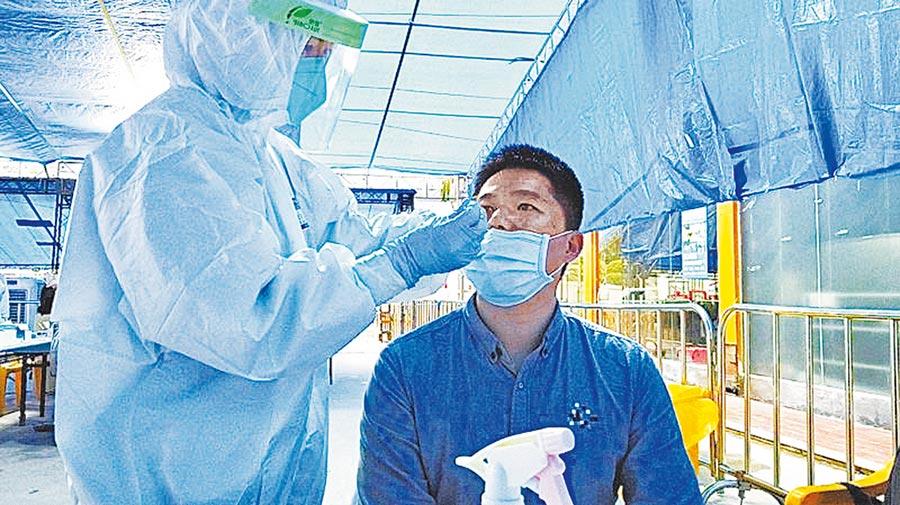旅客正在中轉站檢測區接受鼻咽拭子核酸檢測。(陳晨)
