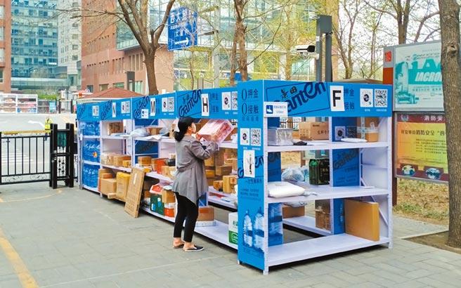 北京宣布將開放讓快遞員進社區。圖為北京民眾在社區庭院的架子取快遞。(記者陳君碩攝)