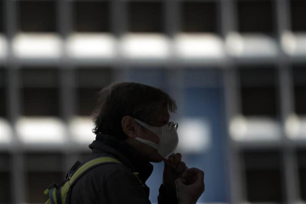 日相安倍砸下466億日圓發給每戶2枚布口罩,不過剛出爐的「安倍口罩」卻因尺寸大小不合,引發民怨。圖為一名正在調整口罩的日本民眾。(美聯社)