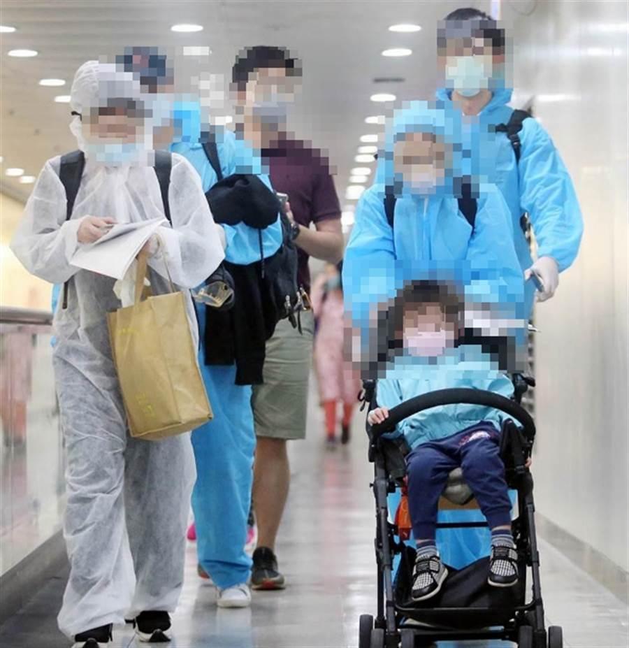 60名滯留在阿拉伯聯合大公國的國人18日搭機抵台,不少人全程穿戴防護衣及護目鏡,降低機上感染的風險。(范揚光攝)