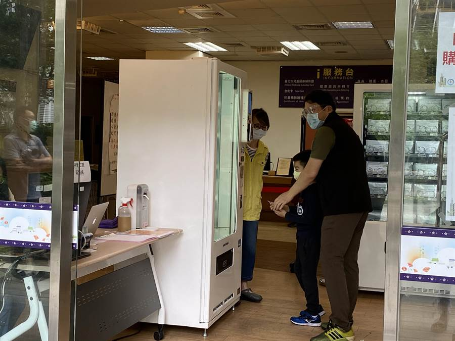 現場的防疫販售人員相當熱心,教小朋友如何操作販賣機。(游念育攝)