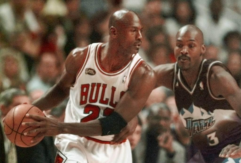 1998年NBA總冠軍賽,公牛隊喬丹(左)持球對抗爵士隊羅素。(美聯社資料照)