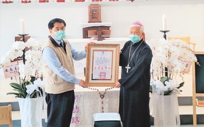 將大半輩子奉獻給台灣早療教育的甘惠忠神父日前於美國辭世,20日在台南學甲舉行的追思彌撒,台南市長黃偉哲(左)到場頒發卓越市民表揚狀。(莊曜聰攝)