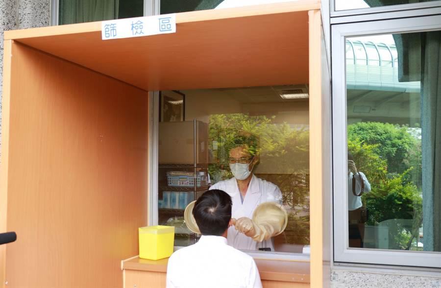 台中慈濟醫院急診科主任李冠儀利用急診室現有空間優勢,將面對室外窗戶玻璃改成壓克力,並在上面開孔裝上手套,保護採檢的醫護人員。(台中慈濟醫院提供/王文吉台中傳真)