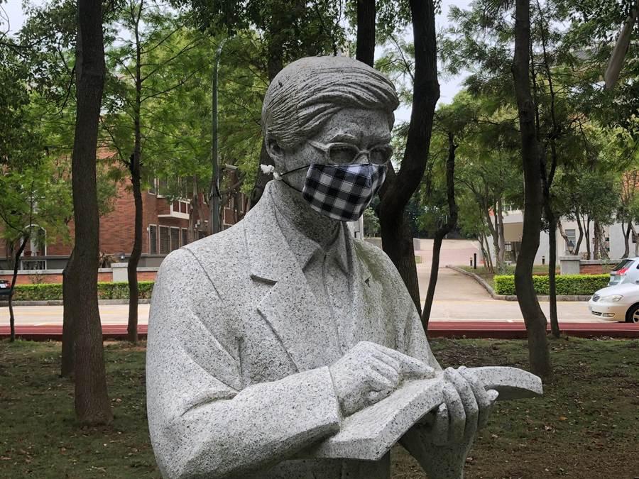 戴上花帔大口罩的鄭愁予大師雕像。(金大提供)