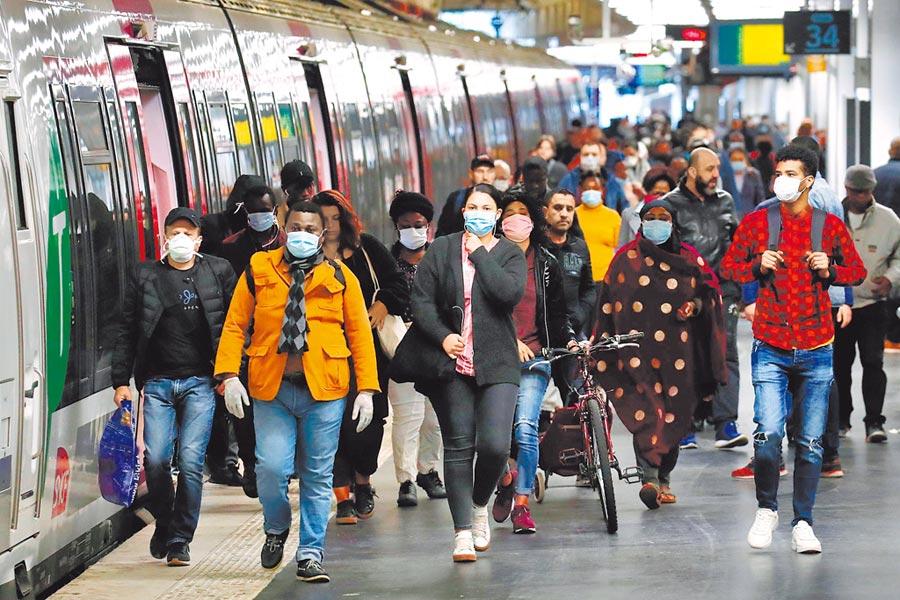 歐洲疫情嚴重的國家包括義大利、西班牙、法國等宣布將逐步解封。其中法國將自5月11日起重開學校、大眾運輸恢復正常營運、供應口罩和消毒劑,但餐館、酒吧、電影院仍暫不開放。圖為巴黎民眾在封城期間戴著口罩進出地鐵站。(路透)