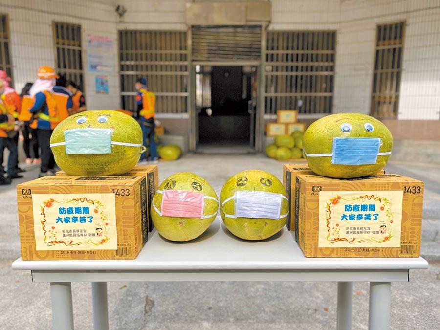蘆洲區長施得仰得知西瓜面臨滯銷,28日下午訂購100顆大西瓜,贈送到轄區各單位,也為西瓜戴上口罩。(戴上容攝)