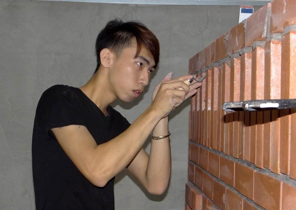 正修科大建築系一年級同學張育銘專注砌磚神情。(林雅惠攝)