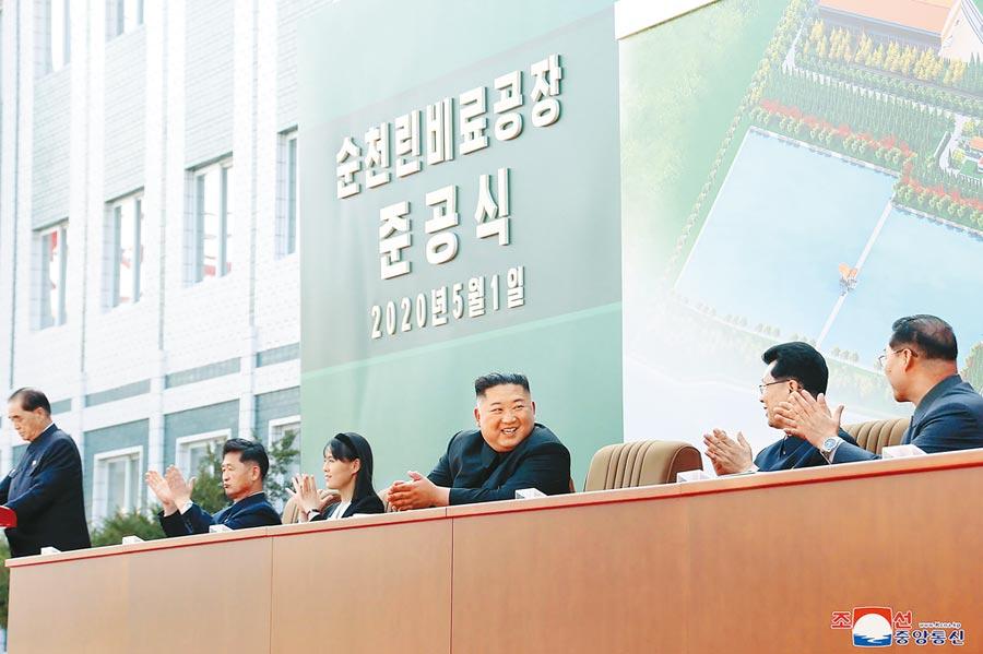 金正恩(右)1日出席順天磷肥廠峻工典禮,其胞妹金與正也坐在一旁。後方看板則有2020年5月1日字樣。(美聯社)