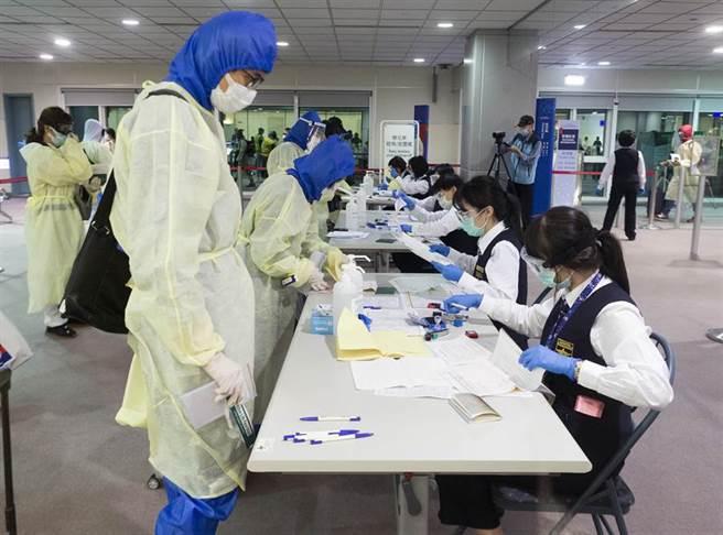 國境疾管人員在候機室內審核旅客健康聲明書與檢疫通知書內容。(陳麒全)