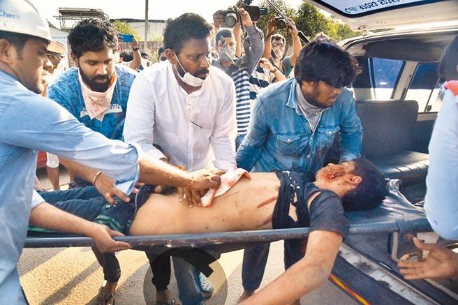 圖為一名吸入有毒氣體的男孩被抬上救護車。(美聯社)