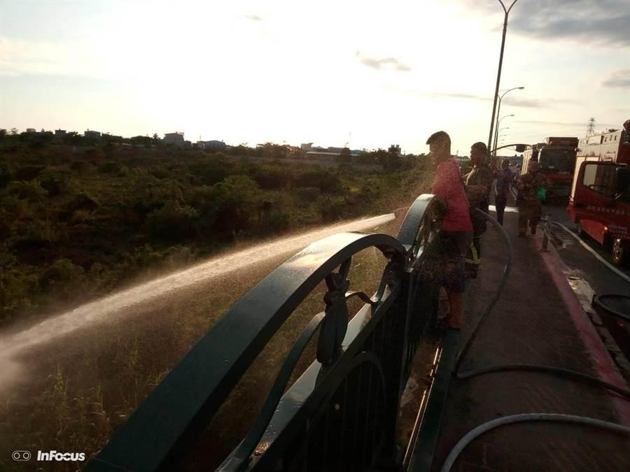 台南麻豆區麻善橋下曾文溪河堤旁有大面積野草樹叢燃燒,消防人員從橋上灑水滅火。(翻攝相片/劉秀芬台南傳真)