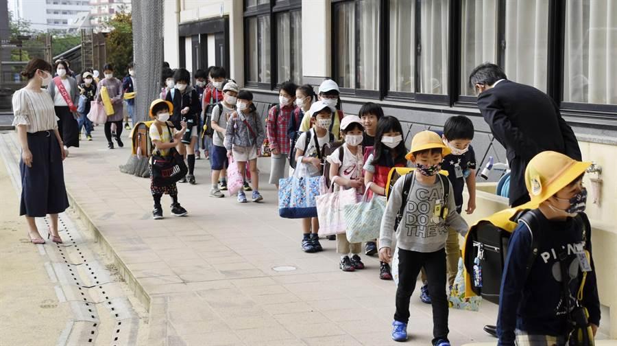 日本新冠肺炎(COVID-19)疫情逐漸緩和下來,九州長崎的小學5月重新開學,要求學生們戴口罩上學。(路透社)