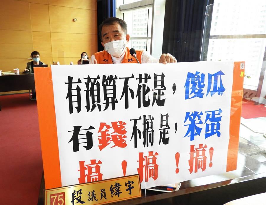 親民黨市議員段緯宇拿出看板說,「有預算不花是傻瓜、有錢不搞是笨蛋」。(陳世宗攝)