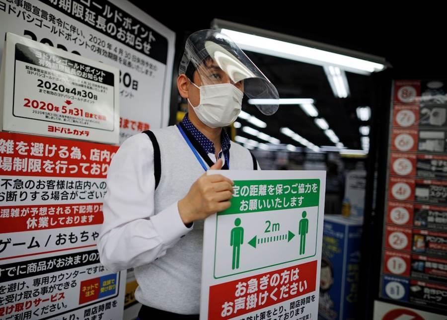 東京的商店店員拿著宣導標示,要求民眾保持距離。(路透社)