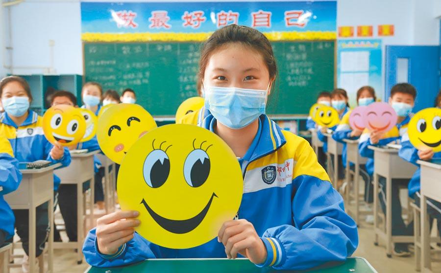 5月7日,河北一中學初三學生開學復課,學生在課堂上展示自己製作的笑臉。(新華社)