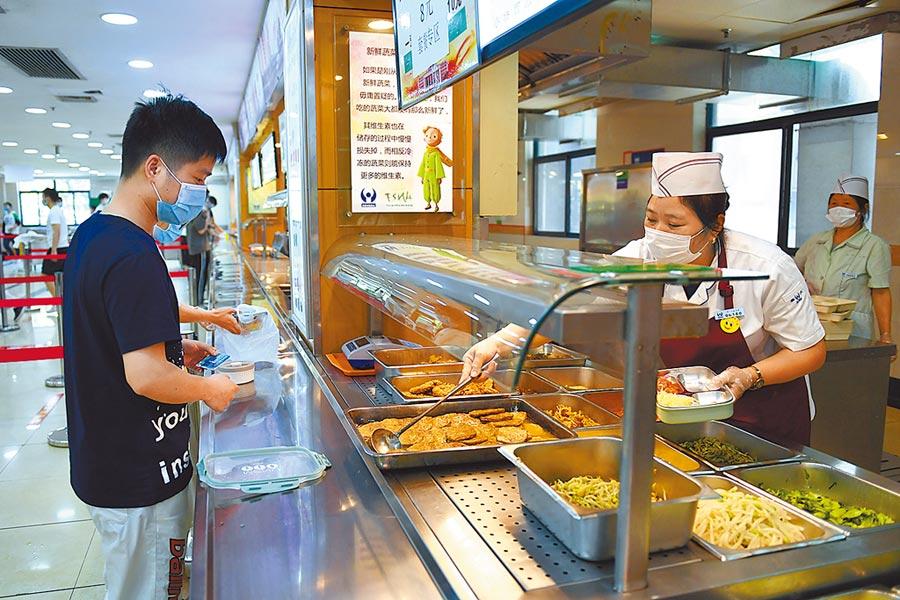 5月12日,浙江工業大學食堂工作人員在為校內自帶餐具的師生打包餐食。(中新社)