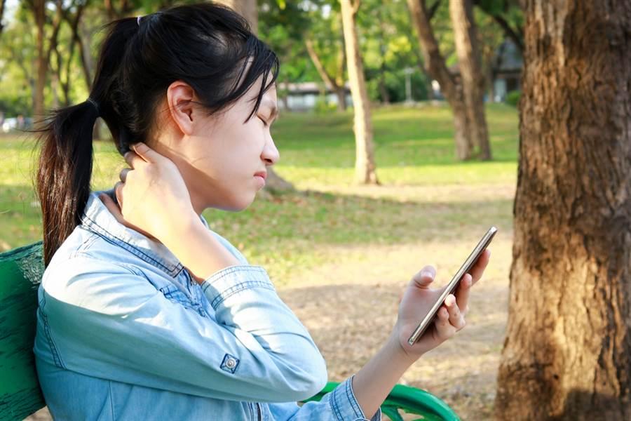 女狂滑手機看防疫資訊,頸部後面又腫又硬,還偶爾會頭痛,醫檢查後發現是「富貴包」。(示意圖/Shutterstock)