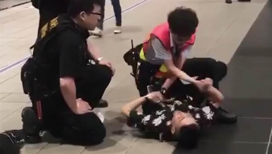 女子不搭運沒載口罩,毆打與咬傷保全,遭壓制在地上。(圖/翻翻YOUTUBE畫面)