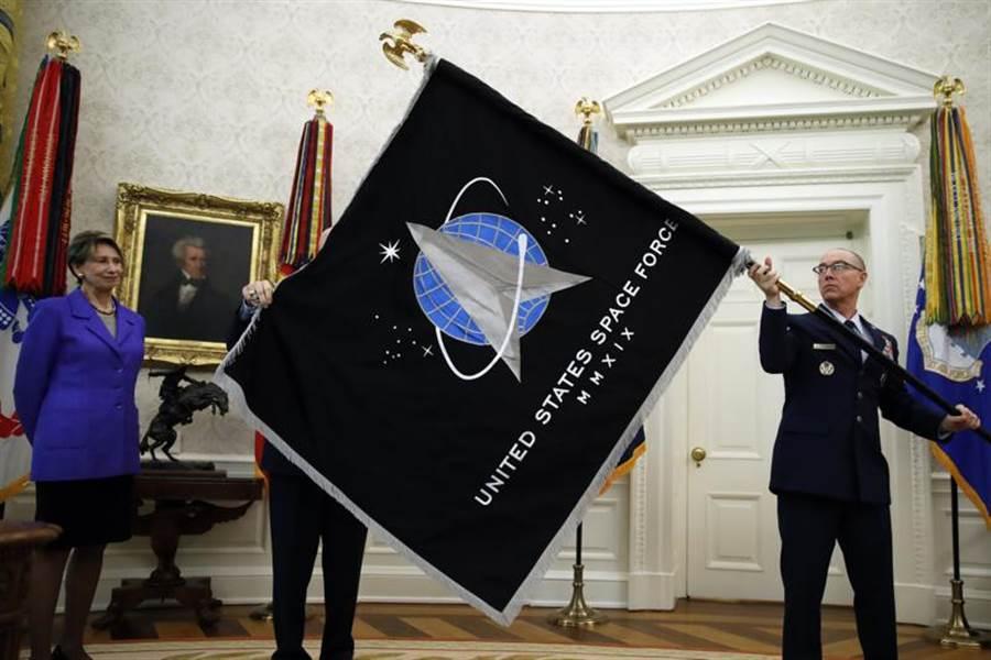 美太空軍在白宮橢圓形辦公室舉行軍旗旗揭旗儀式,這是美軍70年來首面新軍種軍旗。空軍部長巴雷特(左)與總軍士長陶伯曼展示美國太空軍的軍旗。(圖/美聯社)