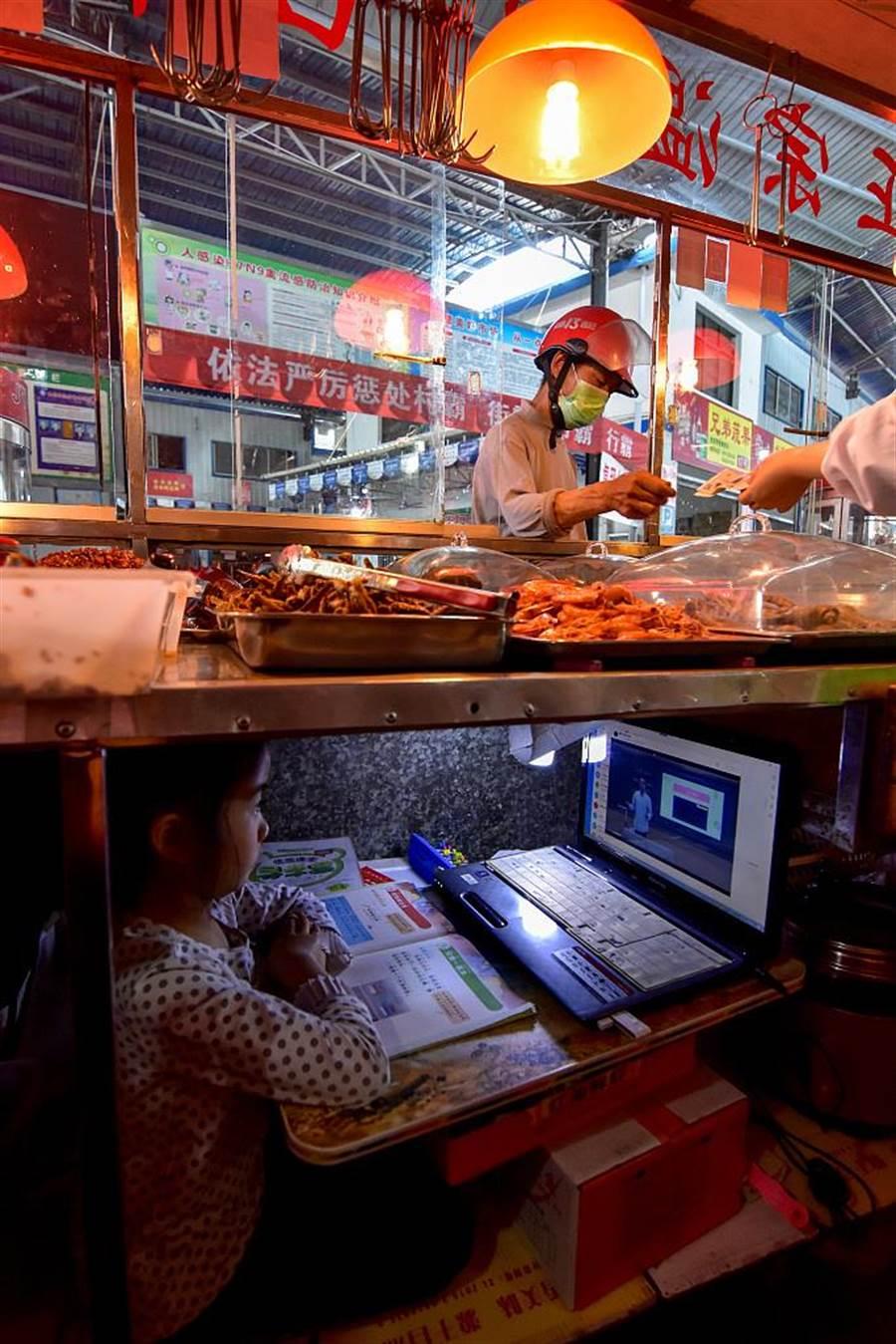 柯媽媽親自騰出攤車底下的空間,添購一台舊式筆電和檯燈,讓她能夠邊工作,邊陪著女兒上網學習。(摘自推特CGTN)