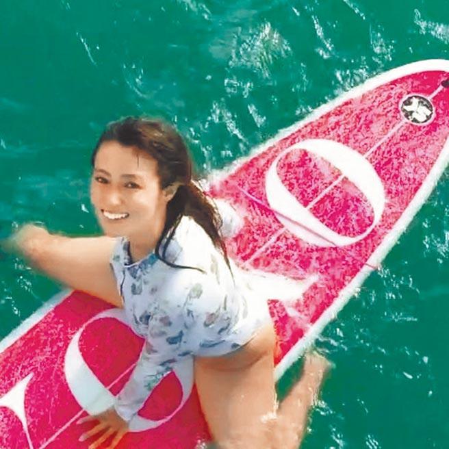 深田恭子在寫著「恭子」的衝浪板上展現海上風情。(摘自IG)