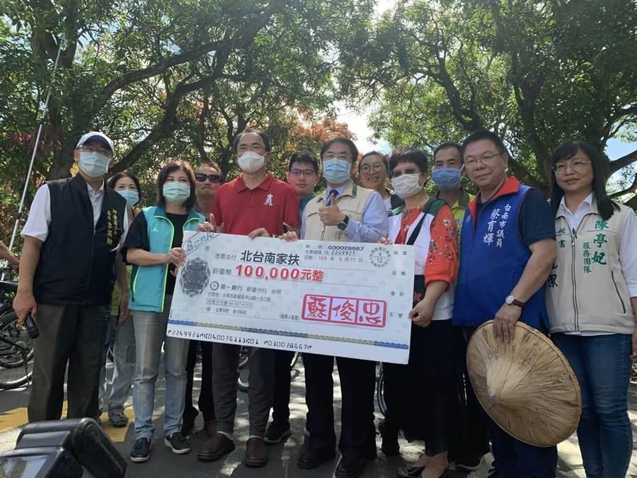 台南東山出身的企業家蘇敬宗(紅衣者),共捐出40萬元給北台南、南家扶中心。(莊曜聰攝)