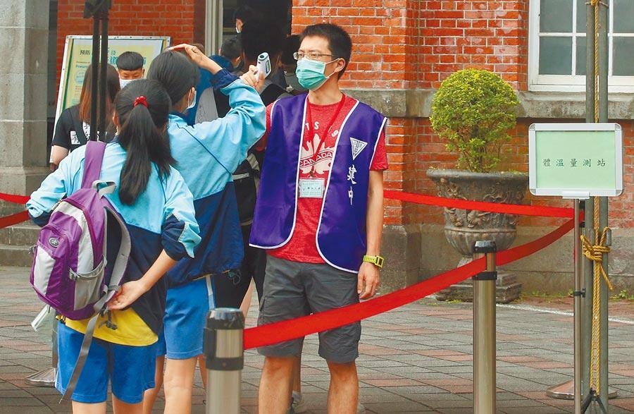 台北市建國中學考場,考生們依照考場人員要求出示准考證,然後量體溫進入考場。(趙雙傑攝)