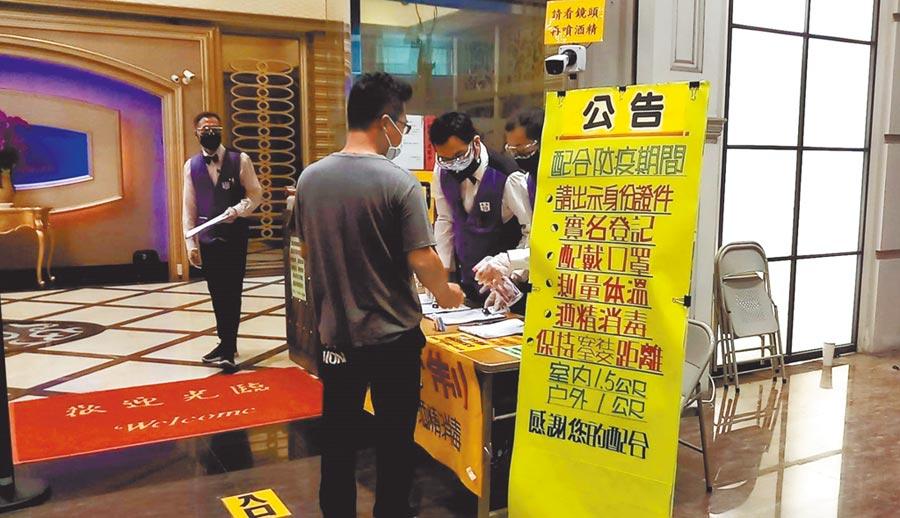 台南市萬象舞廳復業,客人須戴口罩、量額溫且採實名制才能進入,並由工作人員幫客人噴酒精消毒雙手。(程炳璋攝)
