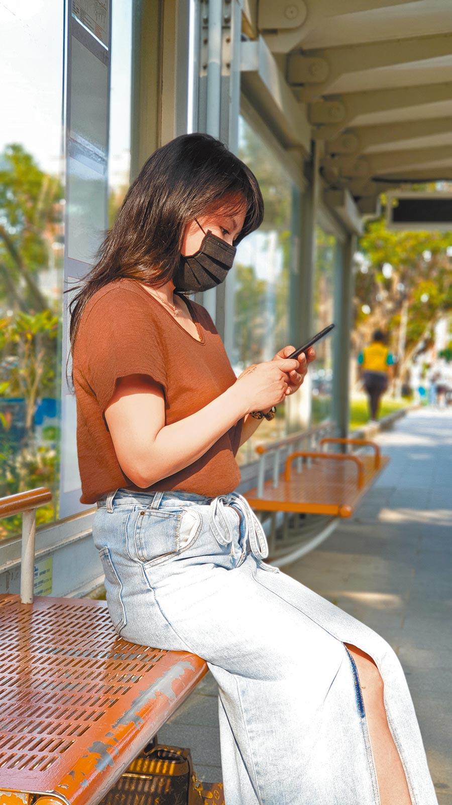Jenny滯留武漢95天,返台後又集中隔離14天。她在台北街頭的公車亭等候公車時邊滑手機邊享受午後的陽光,對人生有了更深的體悟。(藍孝威攝)
