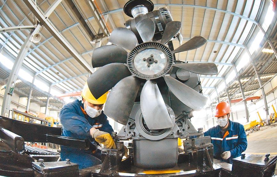 大陸經濟學家林毅夫表示,大陸有能力使今年下半年GDP增速達到15%。圖為江蘇連雲港海州經濟開發區內的一家勘探技術有限公司的工作人員在生產車間組裝工程鑽機。(新華社)