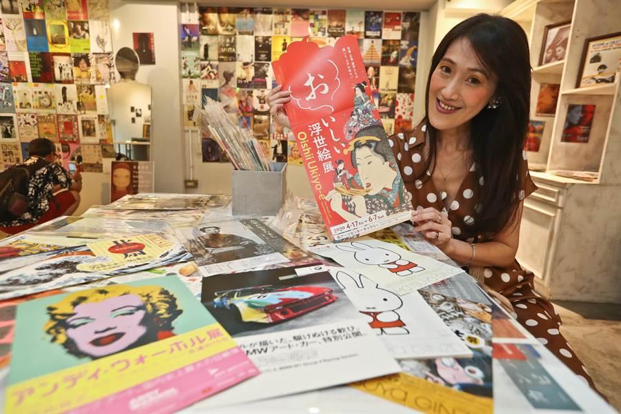 舊香居店主吳雅慧拿著今年日本森藝術中心畫廊的浮世繪展的DM,由於展覽主題與『吃』相關,DM上設計一個人吃烤鰻魚,大喊「おいしい!」。(劉宗龍攝)