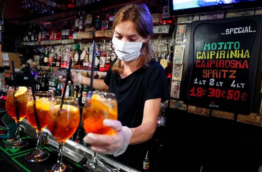 義大利逐步解封,戴著口罩的羅馬酒吧調酒師,準備迎接顧客上門。(路透)