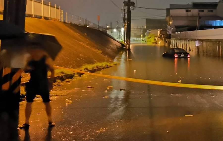 梅雨來襲,中市大里區草堤路219號前21日晚上11點多,一輛黑色汽車行經期間因水淹而拋錨,幸駕駛自行脫困。(中市警局霧峰分局提供/黃國峰台中傳真)